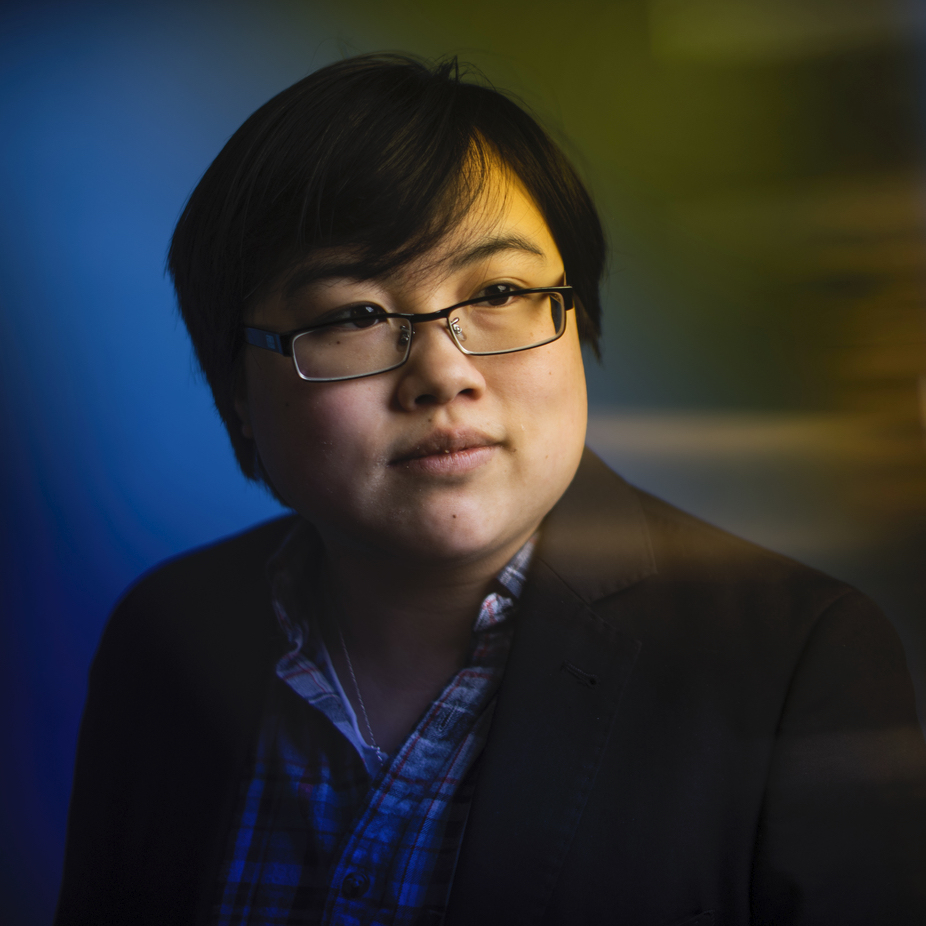 Headshot of Lydia Brown, young East Asian person, with short black hair, wearing glasses, a plaid shirt, and black jacket. They are looking in the distance, posed against a stylized blue dramatic background. Photo by Adam Glanzman.