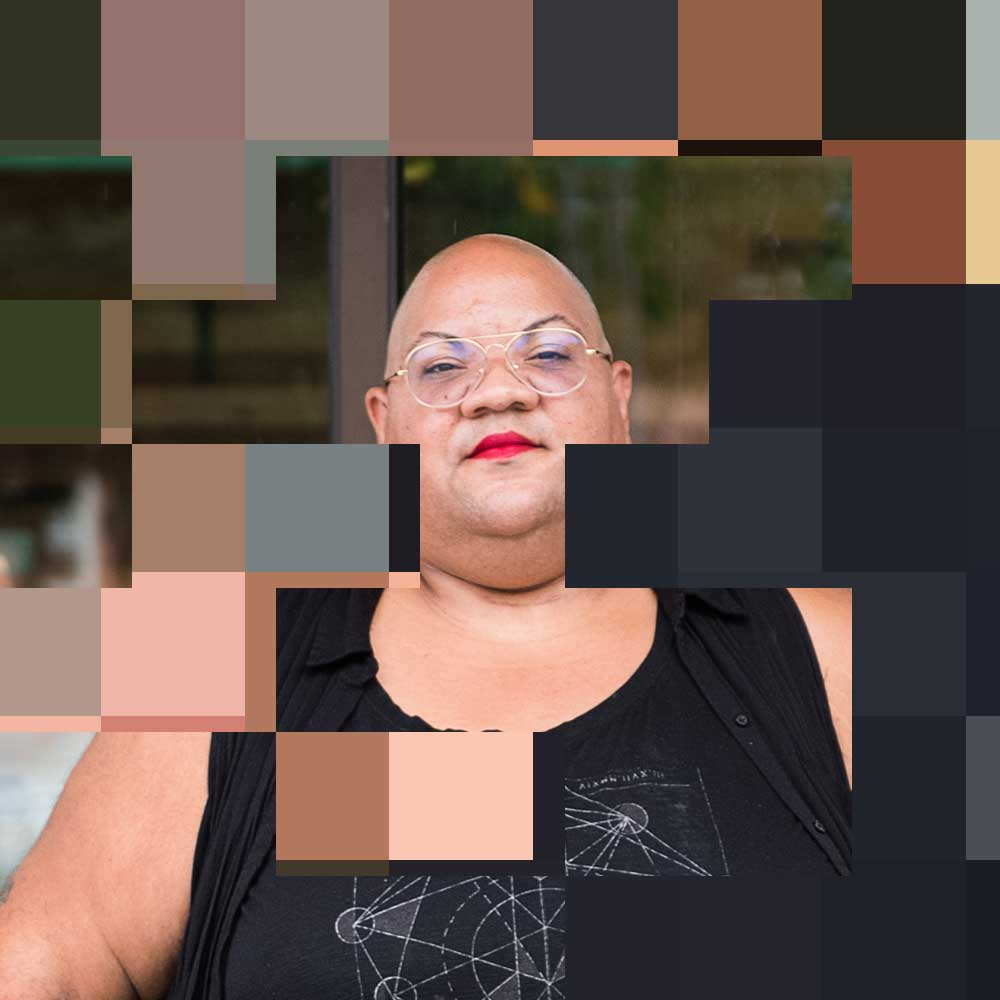 Original photo by Chona Kasinger for the Disabled And Here project. A black non-binary person stands casually outside a cafe, dressed in all black with a shaved head, glasses, a red lip, along with moon earrings. https://affecttheverb.com/disabledandhere/